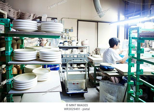 Man sitting in a Japanese porcelain workshop surrounded by shelves with white porcelain plates, ready for decoration