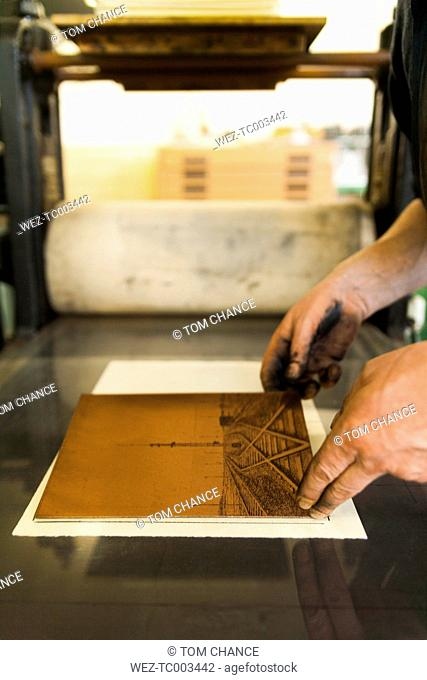 Germany, Bavaria, Mature man picking up copperplate in print shop, close up