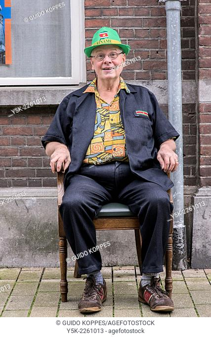 Tilburg, Netherlands. Man sitting in his newly bought chair in front of a facade in the streets