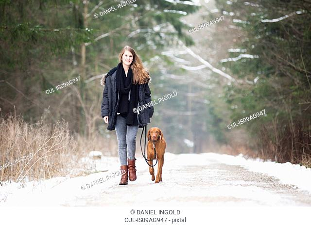 Young woman walking her dog on country road in winter