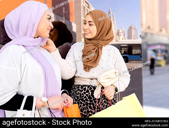 Woman touching headscarf of female friend while standing by glass wall in city