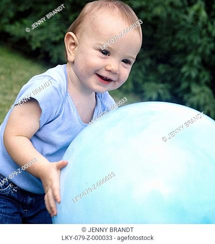 Infant girl playing with large blue ball