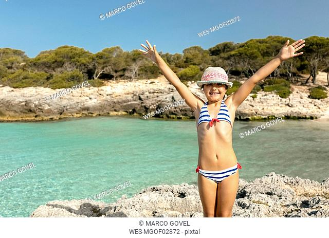 Girl standing at the beach with arms outstretched