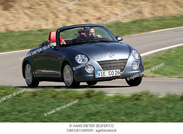 Daihatsu Copen, model year 2006-, anthracite, driving, diagonal from the front, frontal view, country road, open top