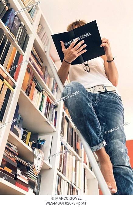 Woman reading a book at bookshelf