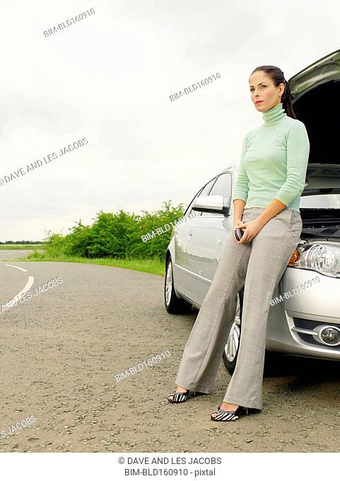 Caucasian businesswoman with broken down car on rural road