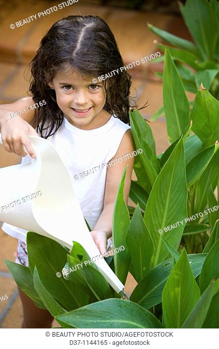 Little girl watering plants at home