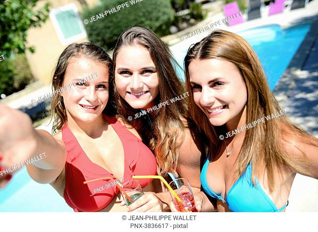 Three beautiful young woman making selfie together by the poolside of resort swimming pool during holiday sunny summer day