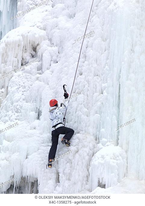 Ice climber climbing a frozen waterfall  Wintertime scenic, Ontario, Canada
