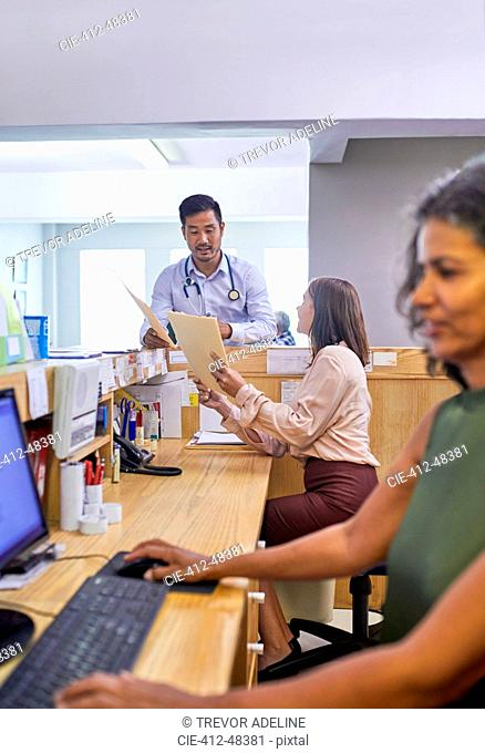 Doctor and receptionist with medical records talking in clinic