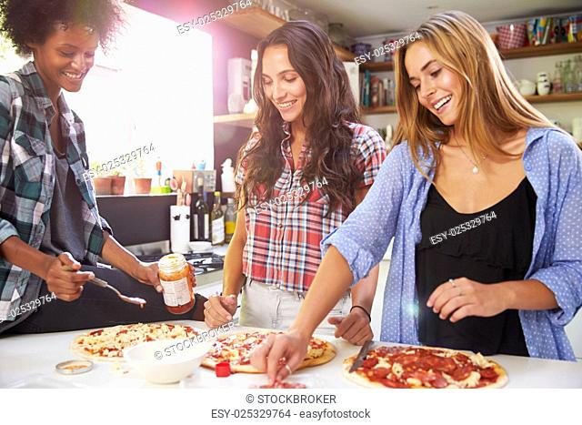Three Female Friends Making Pizza In Kitchen Together