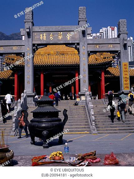 Wong Tai Sin taoist temple established in 1921. Visitors on flight of steps to entrance built in traditional Chinese style with red interior pillars and pagoda...