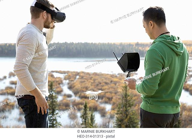 Male friends with drone equipment and virtual reality simulator glasses overlooking lake