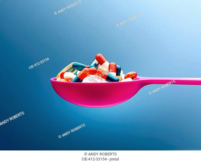Medicine capsules in pink spoon against blue background