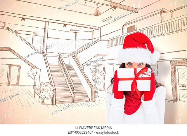 Composite image of brunette in red gloves and santa hat showing gift
