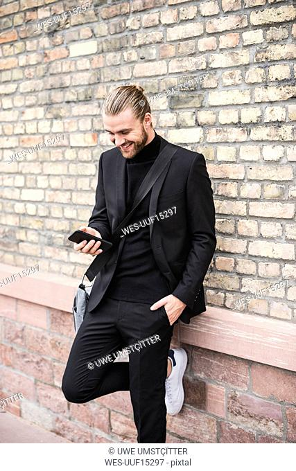 Smiling fashionable young man leaning against brick wall using cell phone