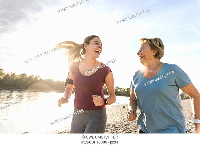 Granddaughter and grandmother having fun, jogging together at the river