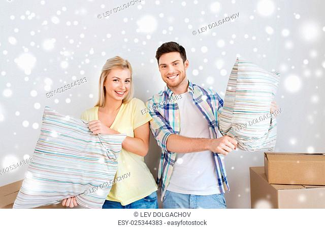 home, people and real estate concept - happy couple pillows moving to new place over snow
