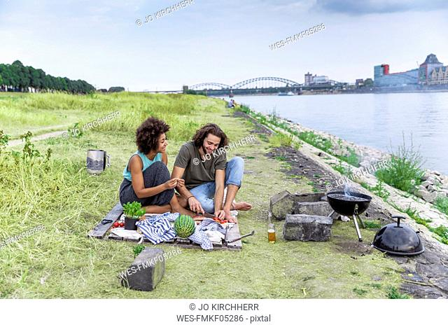 Germany, Cologne, couple having a barbecue at the riverside