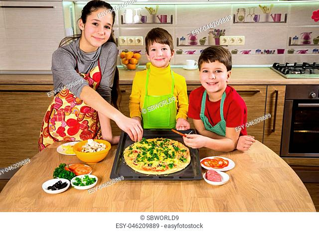 Three kids adding ingredients to raw pizza on tray in the kitchen interior