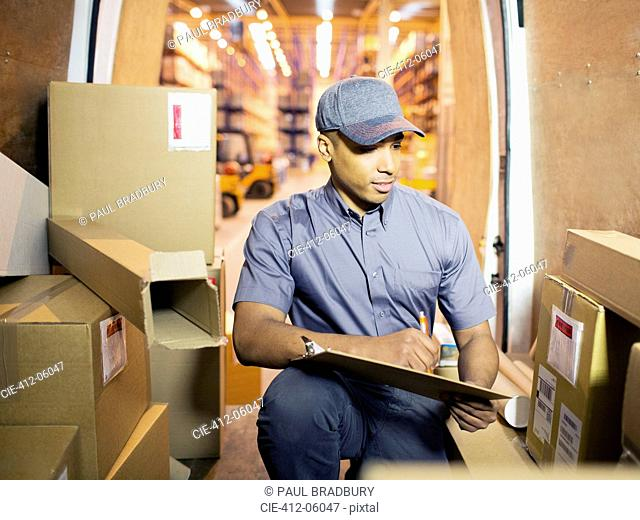 Delivery boy checking boxes in van