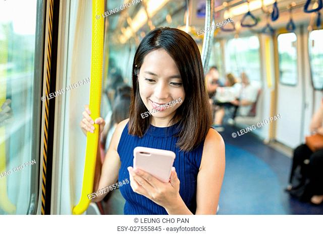 Woman using mobile phone in train