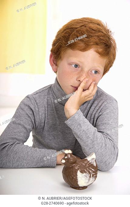 Little boy with red hair, head resting in one hand, thoughtful in front of an easter chocolate hen