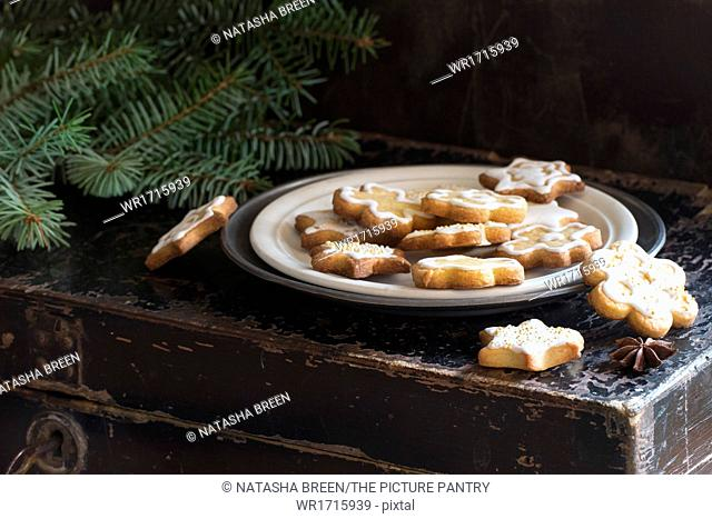 Christmas cookies on old black chest with Christmas tree