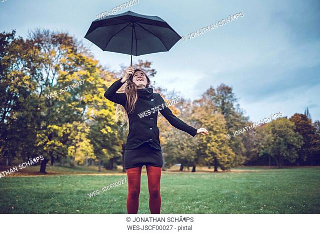 Young woman with umbrella in autumnal park