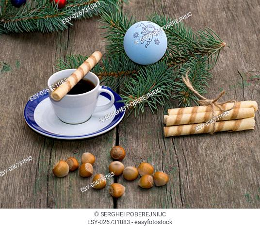 coffee, a fir-tree branch with Christmas tree decorations, nutlets, a subject holidays Christmas and New Year