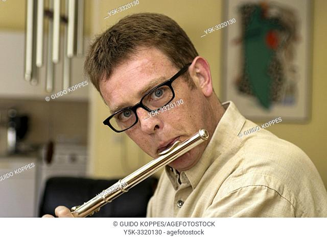 Tilburg, Netherlands. Portrait of a 39 year old male wearing glasses and playing the flute. This music instrument is usually associaled with women