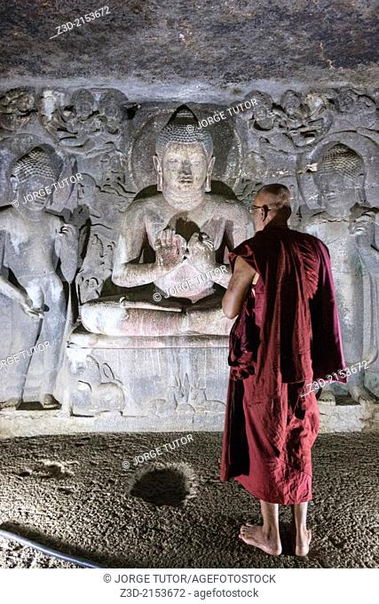 Buddhist monk in front of a sculture of Buddha in preaching attitude. on Cave 6th. Ajanta Cave. UNESCO World Heritage Site, near Jalgaon, Maharashtra, India