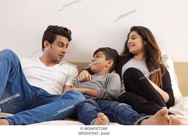 Parents playing with their son on the bed