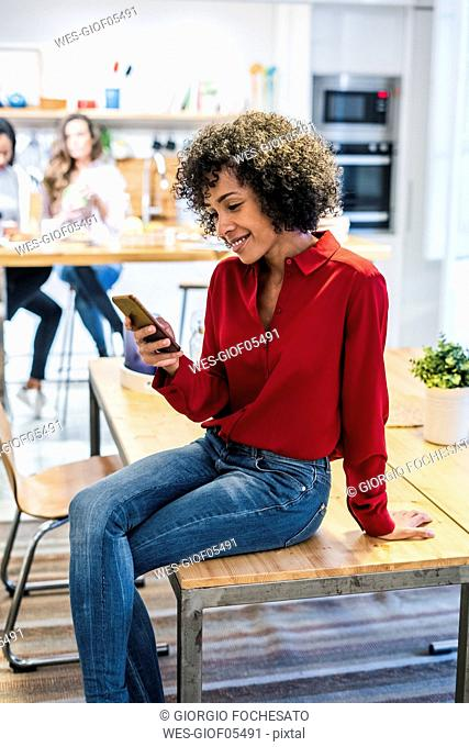 Smiling woman with cell phone sitting on table