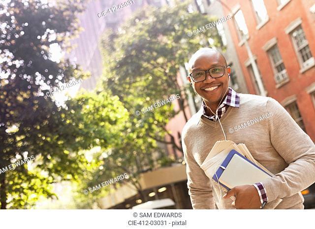 Man listening to earphones on city street