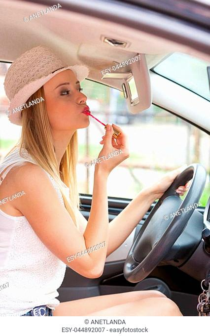 Distracted driver. Young attractive woman looking in rear view mirror painting her lips doing applying make up while driving the car