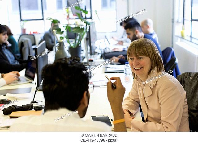 Smiling businesswoman listening to businessman in office
