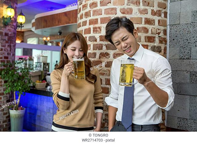 Young smiling businessman and businesswoman drinking beer