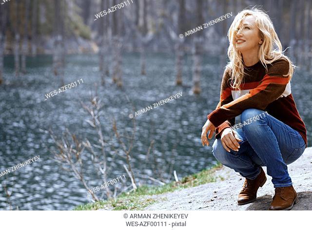 Kazakhstan, Almaty, smiling blond woman at the Lake Kaindy