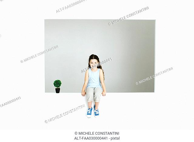 Little girl sitting on ledge, next to plant