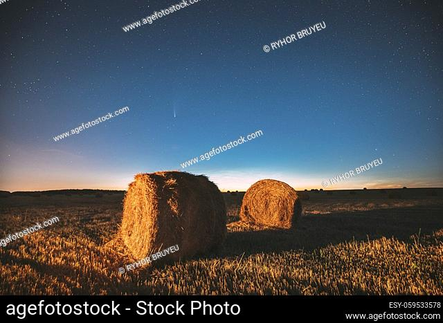 Comet Neowise C2020 F3 In Night Starry Sky Above Haystacks In Summer Agricultural Field. Night Stars Above Rural Landscape With Hay Bales After Harvest