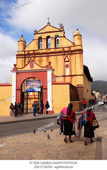 Indigenous vendor walking in front of the Temple of St. Nicolas situated next to the Cathedral of San Cristobal, San Cristobal de las Casas, Chiapas State
