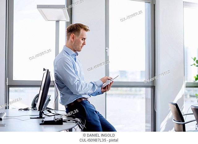 Mid adult businessman leaning against desk using digital tablet touchscreen