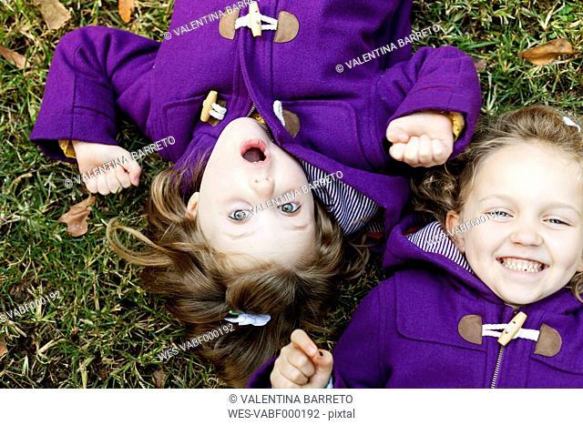 Portrait of little twin sisters lying on a meadow wearing purple coats