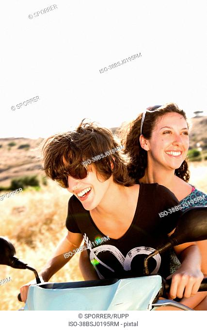Smiling women riding scooter together