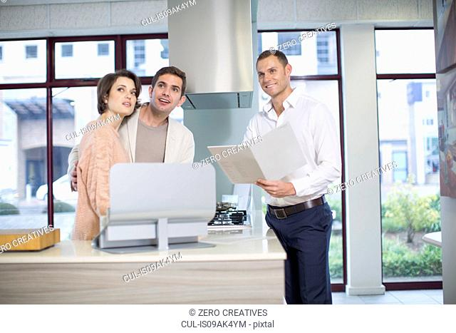 Mid adult couple and salesman looking up in kitchen showroom