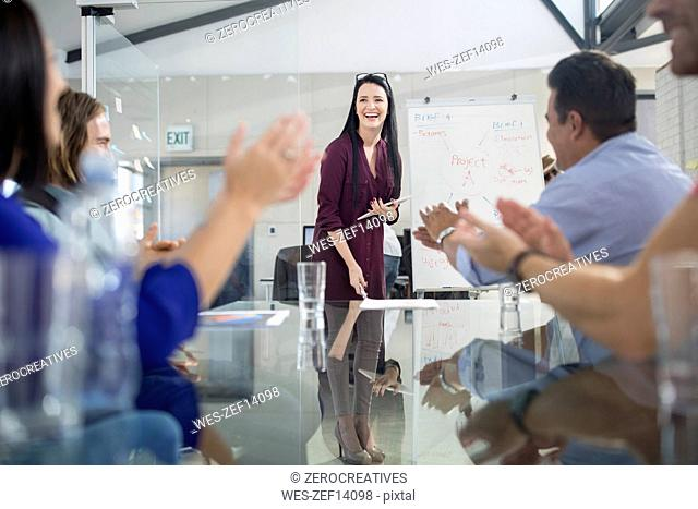 Applause for businesswoman leading a presentation
