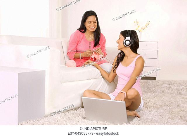 Girl showing mother something on laptop