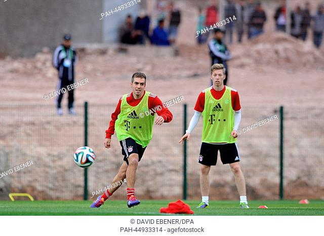 """FCBayern Munich's Philipp Lahm (L) and Mitchell Weiser take part in a training session at the stadium""""""""Stade Adrar"""""""" in Agadir, Morocco, 20December 2013"""