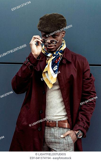 Young african american man in stylish outfit, looking over sunglasses and posing with hand in pocket